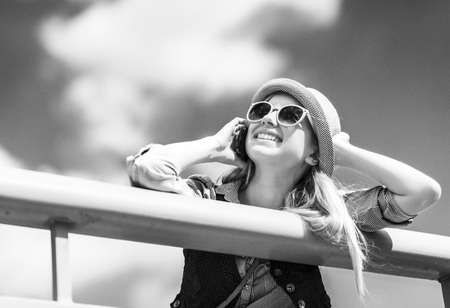 Happy young hipster talking cell phone on city street Stock Photo