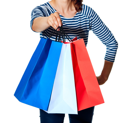 Shopping. The French way. Closeup on trendy woman giving  shopping bags of the colours of the French flag isolated on white giving