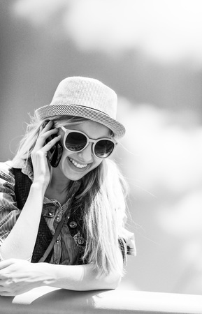 Smiling hipster girl talking mobile phone against sky photo