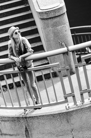 Hipster girl standing on stairs in city photo