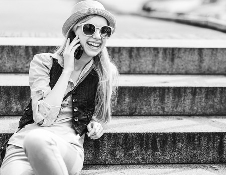 Happy hipster girl talking cell phone while sitting on stairs photo