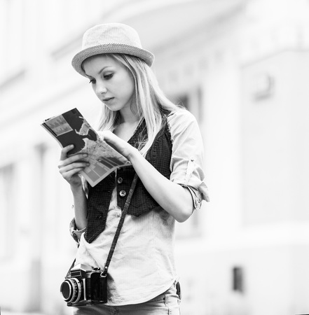 Young woman tourist with map in the city photo
