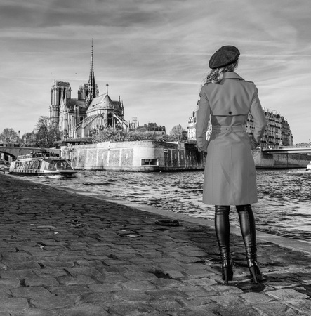 Bright in Paris. Seen from behind elegant woman in red trench coat standing on embankment near Notre Dame de Paris in Paris, France
