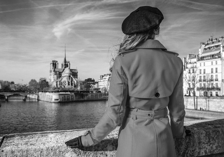 Brilhante em Paris. Visto por trás da mulher na moda em casaco de trincheira vermelho na terraplenagem perto de Notre Dame de Paris em Paris, França