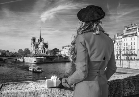 Bright in Paris. Seen from behind trendy tourist woman in red trench coat on embankment near Notre Dame de Paris in Paris, France with Christmas present box Stock Photo