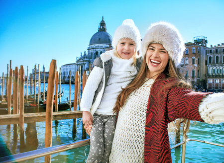 Another world vacation. smiling modern mother and daughter travellers on embankment in Venice, Italy in the winter taking selfie Stock Photo