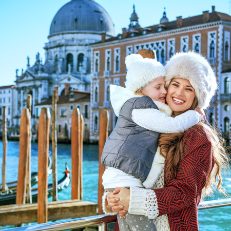 Another world vacation. Portrait of smiling stylish mother and child travellers on embankment in Venice, Italy in the winter hugging