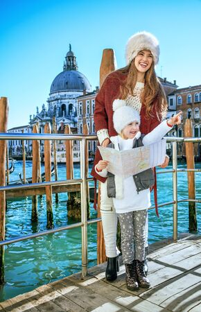 Another world vacation. happy modern mother and child tourists in Venice, Italy in the winter holding map and pointing