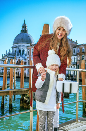Another world vacation. smiling modern mother and daughter tourists in Venice, Italy in the winter taking selfie using selfie stick Stock Photo