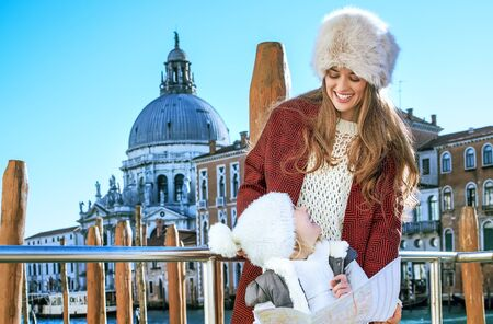 Another world vacation. smiling trendy mother and child travellers in Venice, Italy in the winter with map