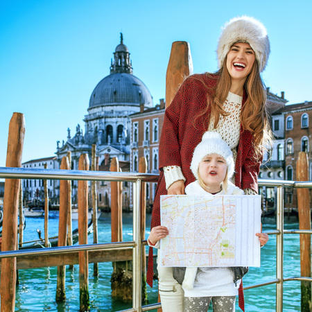 Another world vacation. cheerful young mother and child tourists in Venice, Italy in the winter with map