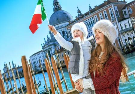 Another world vacation. happy young mother and daughter tourists on embankment in Venice, Italy in the winter rising flag