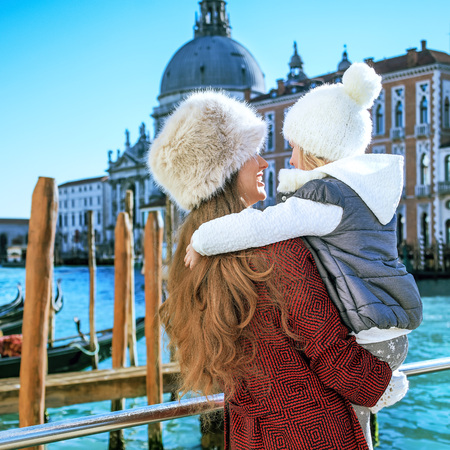 Another world vacation. Seen from behind trendy mother and child tourists in Venice, Italy in the winter embracing Stock Photo