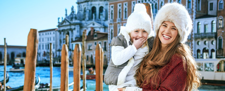 Another world vacation. Portrait of happy trendy mother and daughter tourists in Venice, Italy in the winter Stock Photo