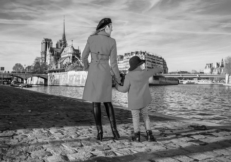 Bright in Paris. Seen from behind stylish mother and daughter travellers in red coats on embankment near Notre Dame de Paris in Paris, France pointing at something Stock Photo