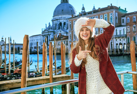 Another world vacation. smiling elegant woman in Venice, Italy in the winter framing with hands Stock Photo