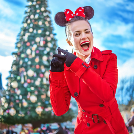 DISNEYLAND, FRANCE - DECEMBER, 8, 2016: smiling young woman in red trench coat in the front of big Christmas tree showing hashtag gesture Editorial