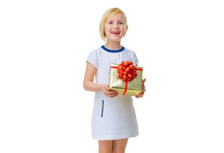 niños vistiendose: Muchacha Moderna. Feliz niño de moda en vestido blanco aisladas sobre fondo blanco que muestra el cuadro de regalo de Navidad Foto de archivo