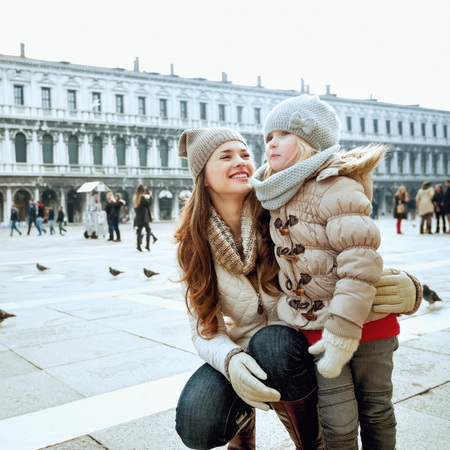 Classical tourist enjoyment in Venice, Italy. happy modern mother and daughter in the winter at San Marco square in Venice, Italy having fun time Stock Photo