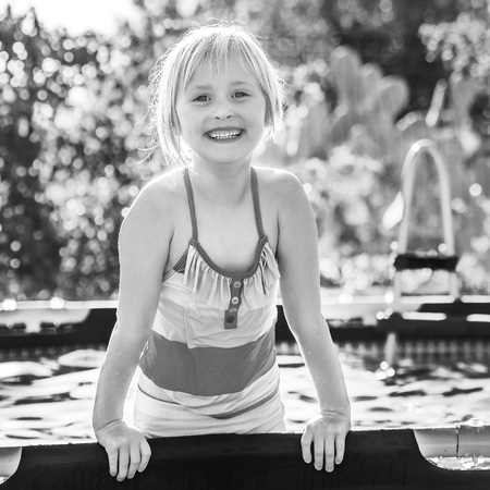 Fun weekend alfresco. smiling active child in colorful swimsuit playing in the swimming pool Stock Photo