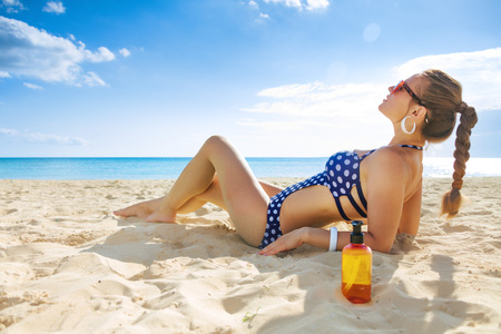 Sun kissed beauty. relaxed active woman in swimwear on the seashore with sun cream