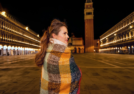 Classical tourist enjoyment in Venice, Italy.  pensive elegant traveller woman wrapped in a long scarf at San Marco square in Venice, Italy in the winter standing near St Marks Campanile Stock Photo