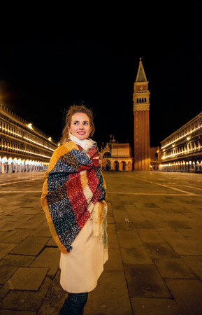 Classical tourist enjoyment in Venice. smiling young traveller woman wrapped in a long scarf at San Marco square in Venice, Italy in the winter looking into the distance near St Marks Campanile 版權商用圖片