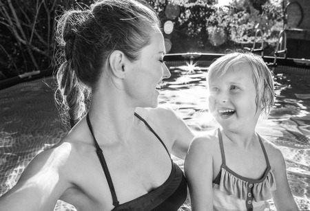 Fun weekend alfresco. smiling healthy mother and child in swimwear in the swimming pool taking selfie Фото со стока