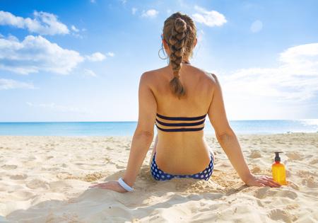 Sun kissed beauty. Seen from behind healthy woman in swimsuit on the seashore sunbathing