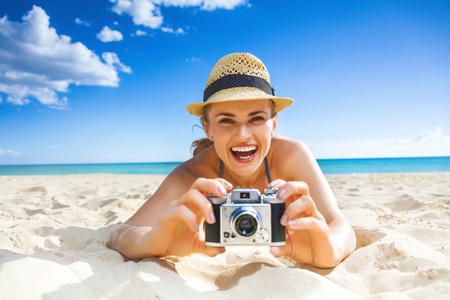 태양이 키스 한 아름다움. 디지털 카메라로 사진을 찍고있는 해변에서 beachwear의 행복한 건강한 여자