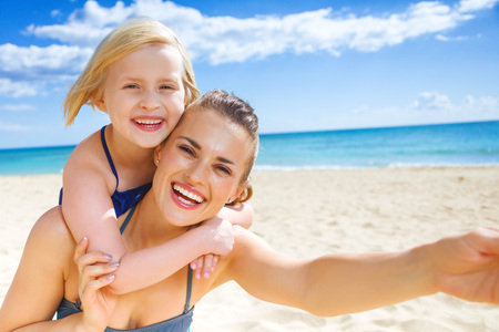 Sun kissed beauty. smiling young mother and child in swimsuit on the seashore taking selfie