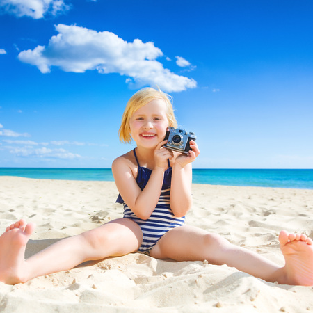 Sun kissed beauty. happy healthy girl in beachwear on the seacoast showing retro photo camera