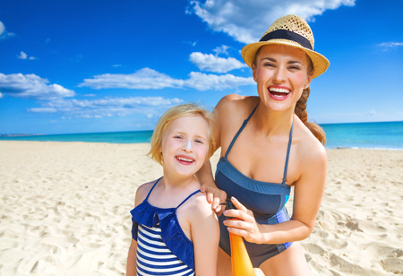 Sun kissed beauty. happy healthy mother and child in swimwear on the seashore applying suntan lotion