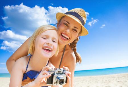 태양이 키스 한 아름다움. 행복 한 젊은 엄마와 레트로 사진 카메라와 함께 해변에서 수영복에 자식의 초상화