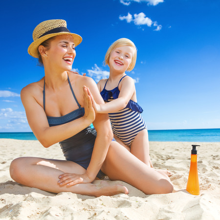 태양이 키스 한 아름다움. 젊은 어머니와 딸 beachwear 해변에서 재생 웃고 스톡 콘텐츠
