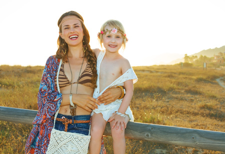 Portrait of smiling bohemian mother and child outdoors in the summer evening sitting on a fence