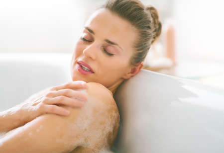 woman in bath: Young woman relaxing in bathtub