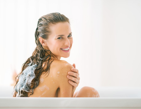 Smiling young woman washing hair in bathtub Stock Photo