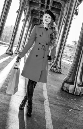 shopper: Full length portrait of young traveller woman in red trench coat on Pont de Bir-Hakeim bridge in Paris with shopping bag Stock Photo