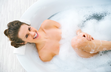 woman in bath: Portrait of smiling young woman laying in bathtub Stock Photo