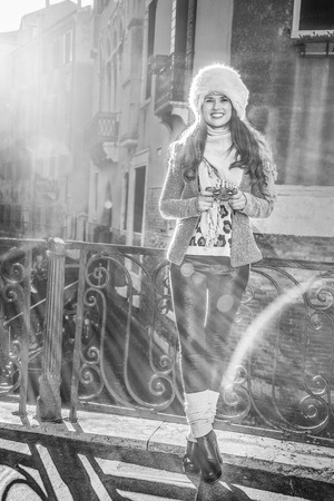Venice. Off the Beaten Path. Full length portrait of smiling modern tourist woman in fur hat in Venice, Italy in the winter writing sms