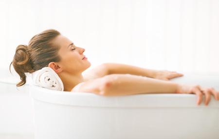 Portrait of young woman relaxing in bathtub Foto de archivo