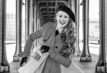 Portrait of smiling stylish woman in red trench coat on Pont de Bir-Hakeim bridge in Paris holding shopping bag and Christmas present box Stock Photo