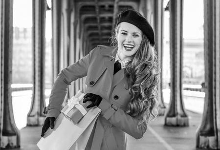 Retrato de mujer elegante sonriente en gabardina roja en el puente de Pont de Bir-Hakeim en París sosteniendo el bolso de compras y caja de regalo de Navidad