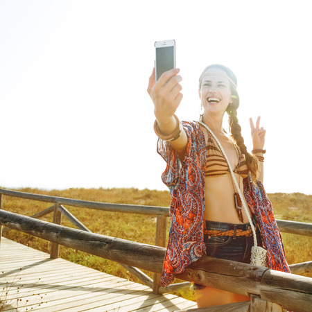 Bohemian vibe vacation. smiling modern free spirit girl in jeans shorts and cape outdoors in the summer evening with smartphone taking selfie and showing victory gesture