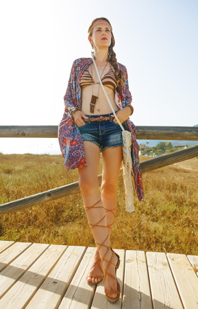 Full length portrait of fashion flower child in jeans shorts and cape outdoors in the summer evening looking into the distance Stock Photo