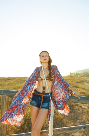 Portrait of young bohemian girl in jeans shorts and cape outdoors in the summer evening looking into the distance Stock fotó