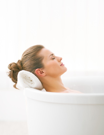 woman in bath: Relaxed young woman laying in bathtub