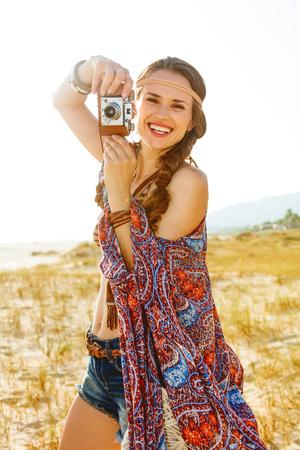 Boheemse vibe vakantie. Portret van gelukkig modieus bohostisje in jeansborrels en kaap in openlucht in de de zomeravond die retro fotocamera houden