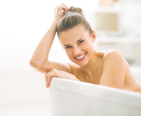 Portret van lachende jonge vrouw in badkuip
